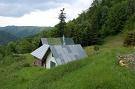 V pozadí zatrávnená plocha, kde stála drevenica Juraja Blaščaka v osade Baranie
